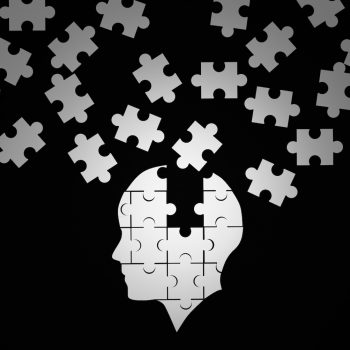 White jigsaw puzzle as a human brain on black. Huntington's Disease