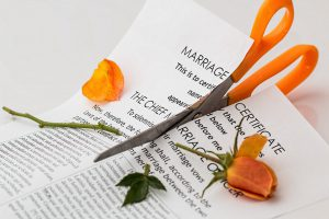Scissors cutting through a piece of paper that says marriage of certificate and an orange rose on top of the paper.