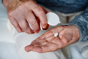Older caucasian man's hand dropping a pill onto his palm from a pill bottle.
