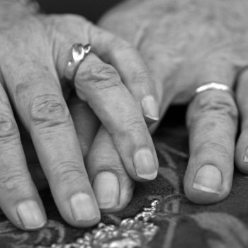 Hands of an elderly couple married for over 60 years heading to gray divorce