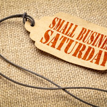 Small Business Saturday sign - a paper price tag with a twine iagainst burlap canvas