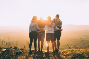 four adult friends looking into the sunset