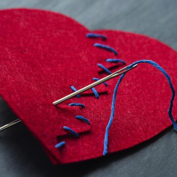 Broken heart sewn together with needle and thread