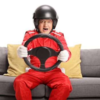 senior man holding steering wheel on couch