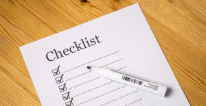white paper that says checklist with boxes down a line with checkmarks in them.