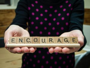 the word encourage spelled out with scrabble pieces being help by a little girl's hands.
