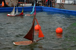 Baots in water floating around red balls