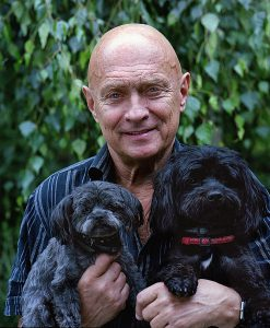Older caucasian man smiling while holding up two black dogs.