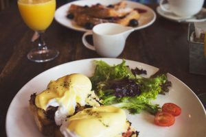 eggs benedict on a plate with some leafy greens.