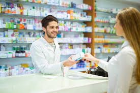 Caucasian man dressed in a white coat handing out medicine to someone.