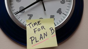"""post it note with """"time for plan B"""" on it stuck to a clock."""