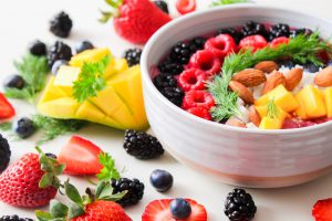 White bowl filled with fruits and nuts surrounded by more fruit on the table, for psoriasis diet.