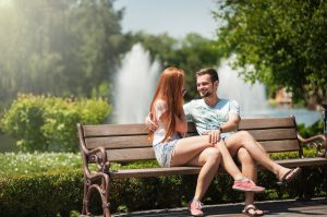 Young caucasian man and woman sitting on a park bench talking.
