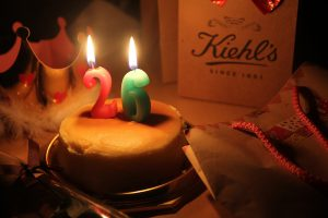 """Birthday cake with canles """"26"""" on it lit."""