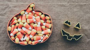 Candy corn in a pumpkin shaped plate.