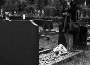 black and white funeral photo with grave and flowers