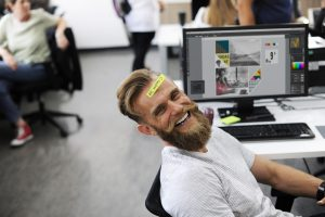 "Young caucasian man with a beard at work smiling with a sticky note on his head that says ""be happy"""