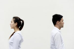 An asian woman and man with their backs towards each other.