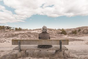 Woman with gray hair sitting on a bench looking out into the dessert.