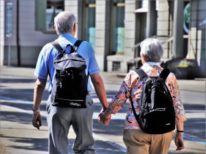 The back of an older man and woman with black backpacks on holding hands while walking.