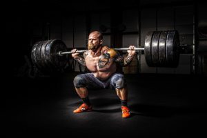 man squatting heavy weight and straining for men's health