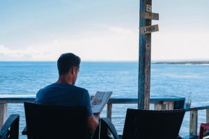 business owner reading a book by the ocean on a porch