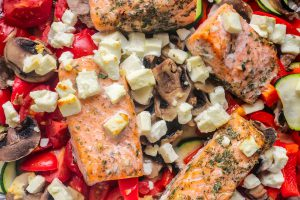Cooked salmon laying on a bed of tomatoes with mushrooms and cheese on top.