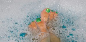 Caucasian woman's toes painted lime green in soapy bath water.