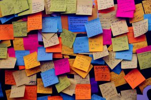 Different colored post it notes on top of each other on a wall.