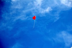 Red heart balloon floating in a blue sky. long-distance