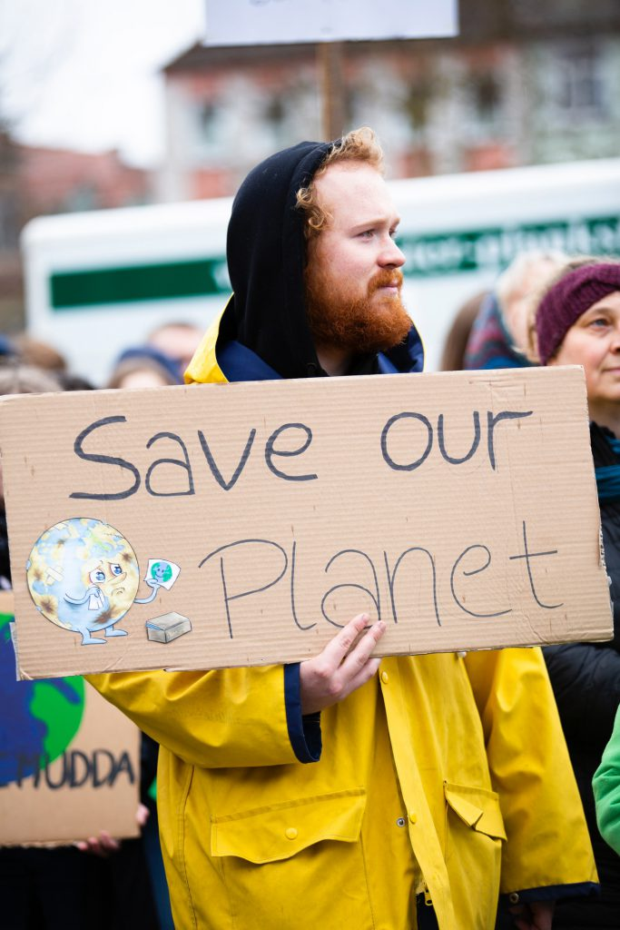 save our planet sign held by an activist
