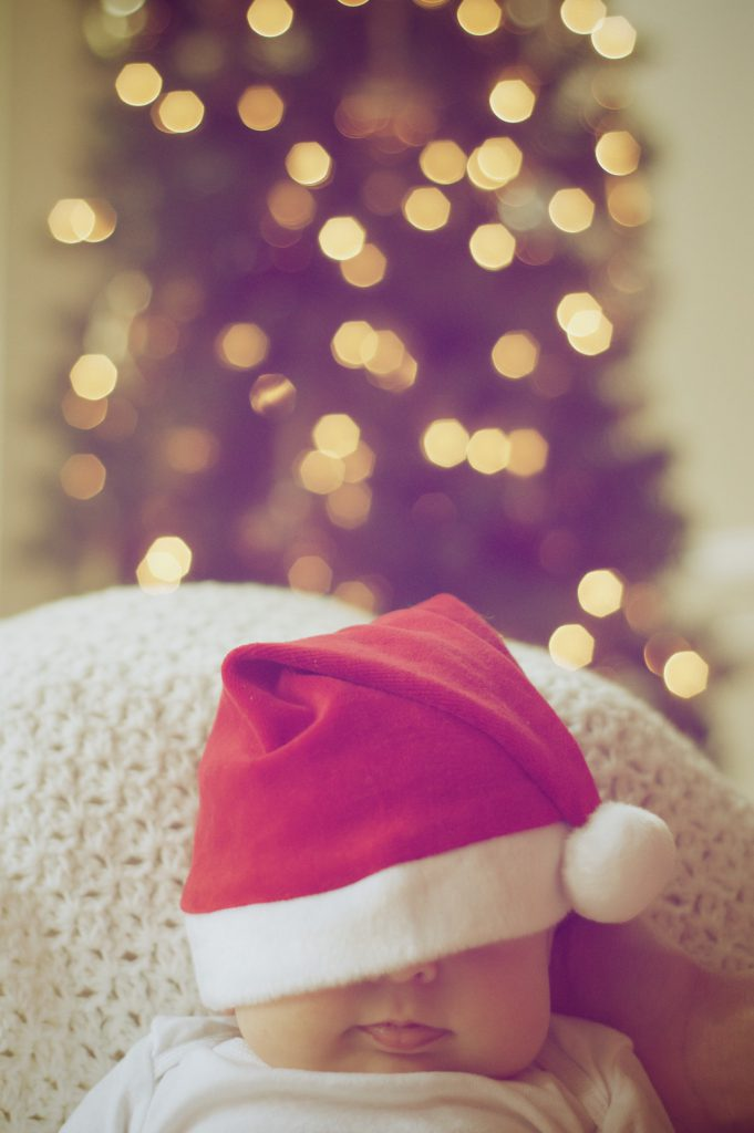 baby with santa hat with a lit tree in the background