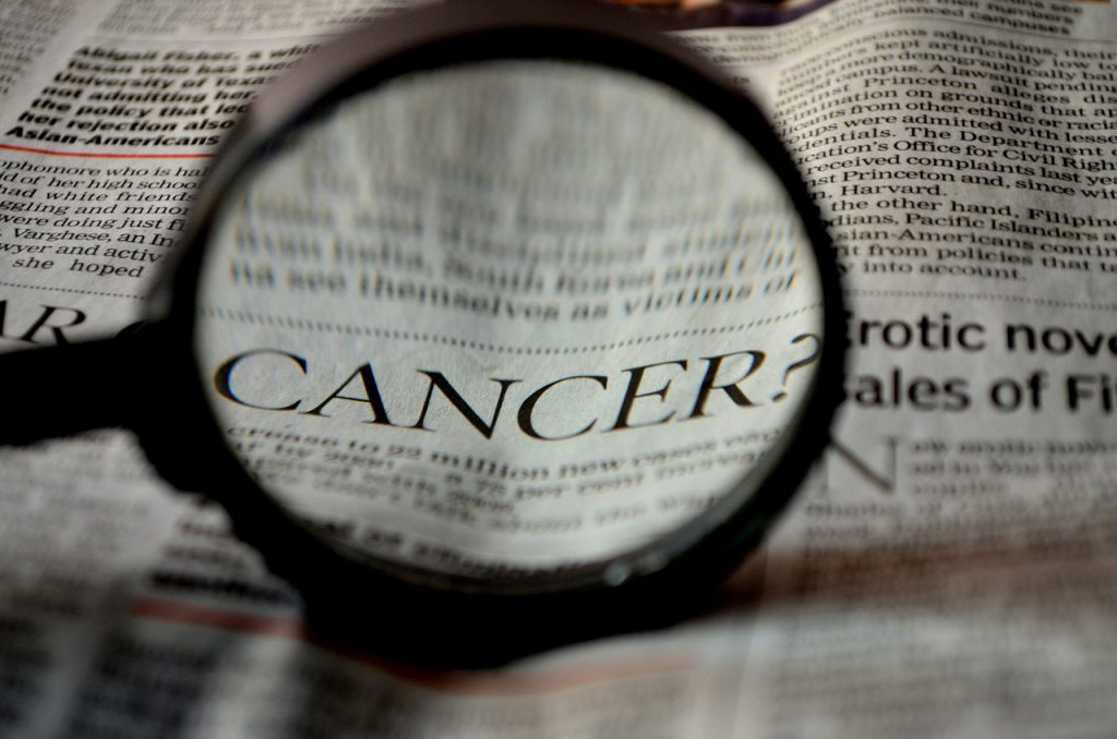 "the word ""cancer"" in a newspaper article magnified by a magnifying glass"
