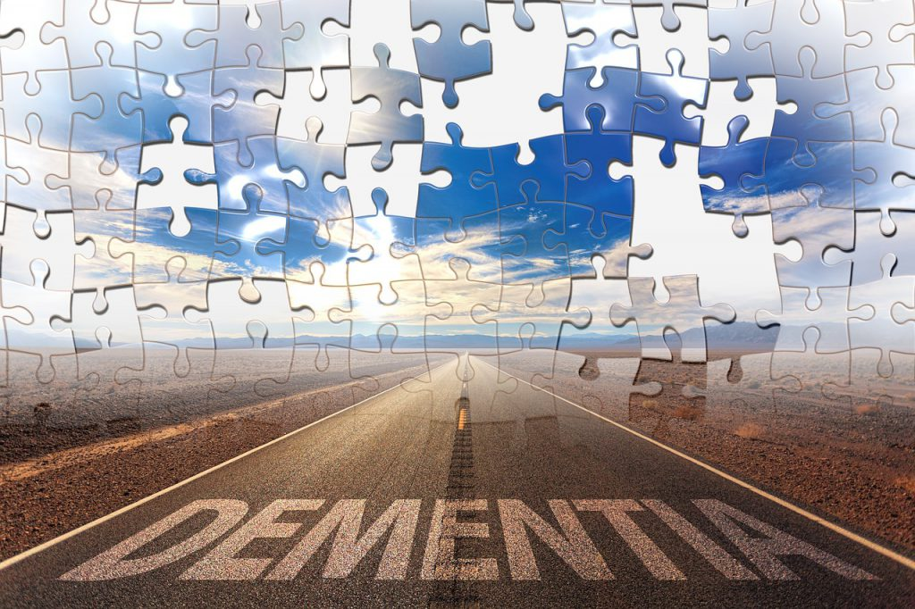 A road with the words dementia on it, and the wky in puzzle pieces with pieces missing.