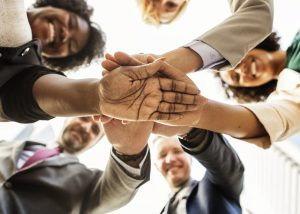 A group of employees standing in a circle with their hands on top of one another. Camera view is looking up at their palms.