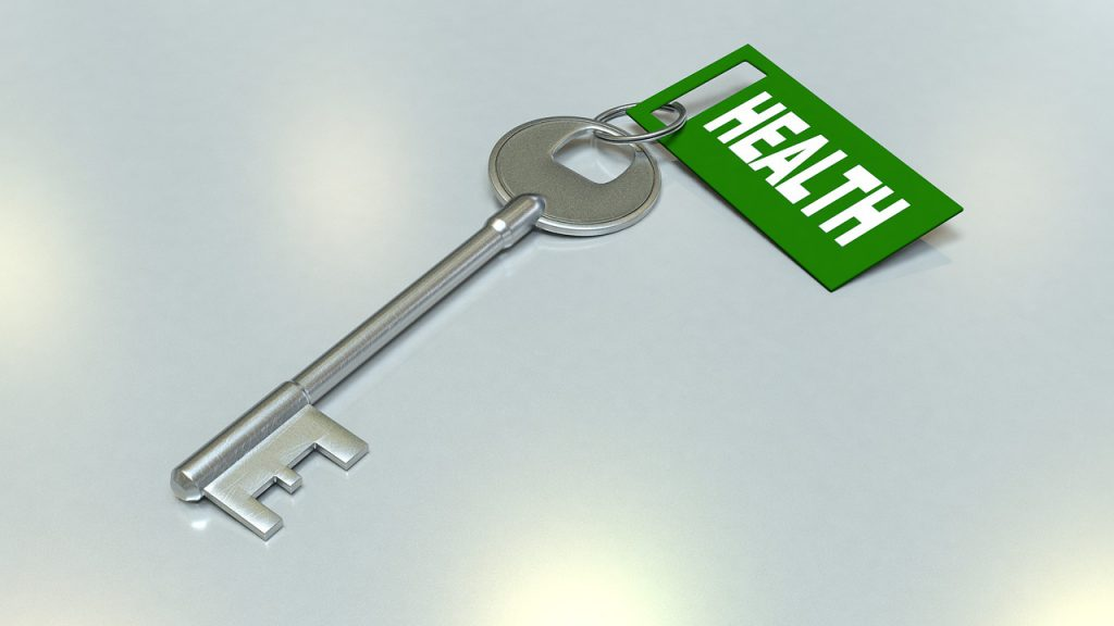 """A slver key with a green tag on it that says """"health"""""""