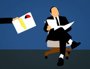 Cartoon of a man in a suit sitting on a chair with papers in his hand, with another hand in the picture giving paperwork to man sitting down.