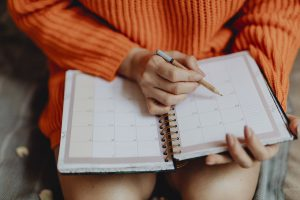 Caucasian woman's torso sitting down in an orange sweater with a planner on her lap writing in it.
