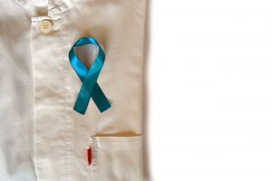 Blue ribbon placed on top of a folded white collared shirt for prostate cancer