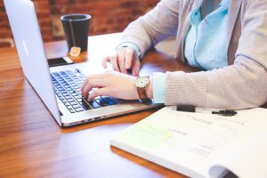 Woman sitting at a table in front of a laptop with a black cup of tea on her rigt and notebook on left.