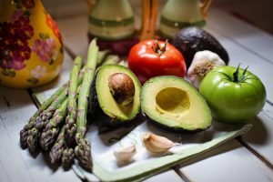 Avocado, asparagus, red tomato, green tomato, and garlic cloves on cutting board.