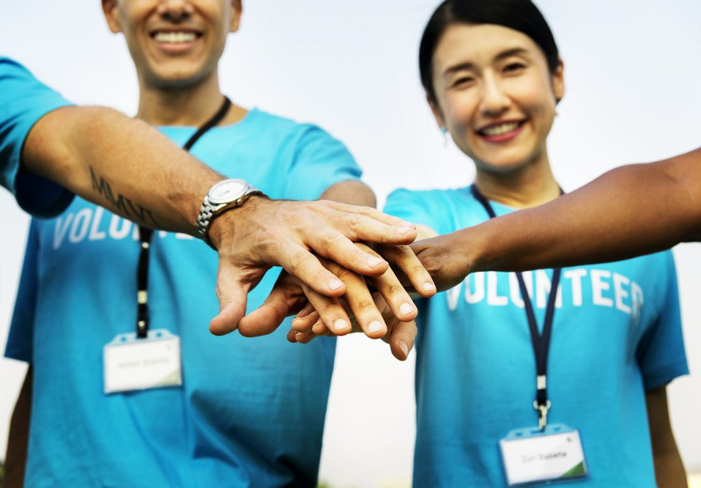 """Asian woman and caucasian man with blue shirts on that say """"volunteer"""" putting their hands in a huddle."""