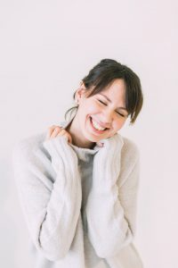 woman smiling in a sweater about menopause solutions