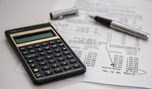 calculator, pen, and chart for an HSA or FSA