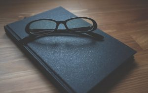 glasses sitting on a book for insurance contracts