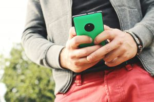 person with red pants emailing from their phone