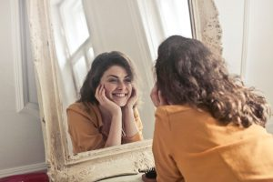 woman using a mirror for optimism