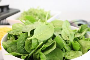 Bowl of spinach on a table.