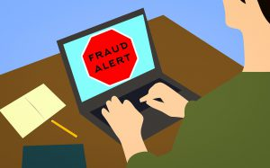 """cartoon of a person sitting in front of a laptop with """"fraud alert"""" on the screen"""