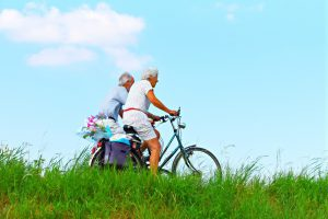 two elderly people riding bikes